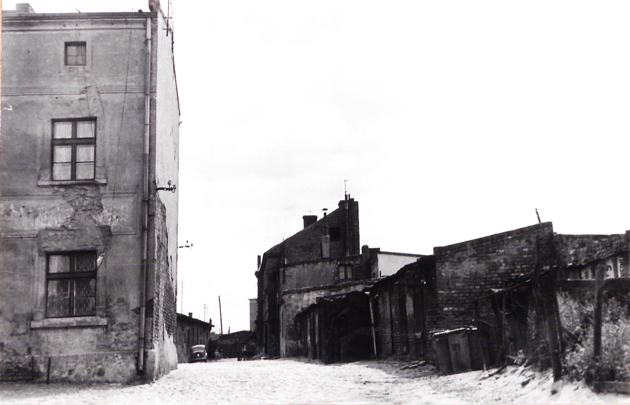 czarno-biała fotografia zabudowania brukowana ulica samochód w oddali zdjęcie zrobione w 1963 roku