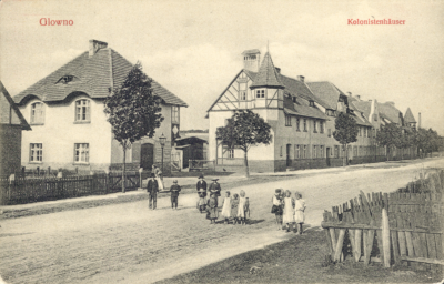 Glowno. Kolonistenhäuser. Jednoobrazkowa karta pocztowa z widokiem kolonii Karlsbunne przy ul. Gnieźnieńskiej. Osiedle zostało wybudowane w 1906 roku z inicjatywy Deutsche Arbeiter-Wohnungsgenossenschaft (Niemiecka Robotnicza Spółdzielnia Mieszkaniowa), pomiędzy Pudewitzerstrasse (ul. Pobiedziską, dziś Gnieźnieńską), a rzeką Główną. Składało się z domów typu willowego dla majstrów i urzędników miejskich oraz podłużnego budynku wielorodzinnego wzdłuż ul. Gnieźnieńskiej, przeznaczonego dla robotników. W 1919 roku osiedle zostało zakupione przez Zakłady Cegielskiego. Ze zbiorów Biblioteki Uniwersyteckiej w Poznaniu.