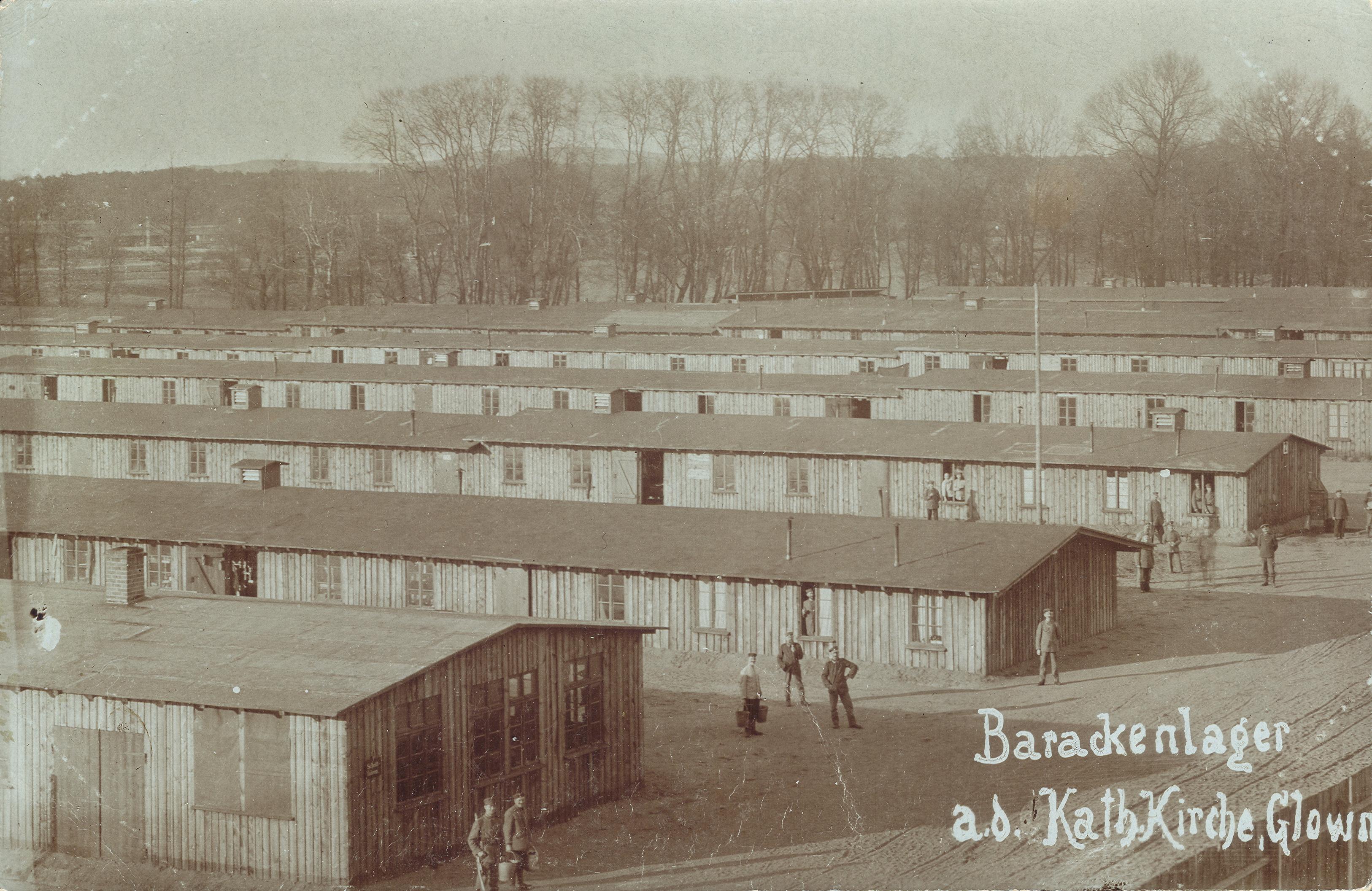 Barackenlager a.d. Kath. Kirche, Glowno. Fotografia przedstawiająca koszary wojskowe (kompleks baraków obozu wojskowego wraz z komendanturą) znajdujące się niedaleko kościoła katolickiego na Głównej. Ze zbiorów Biblioteki Uniwersyteckiej w Poznaniu
